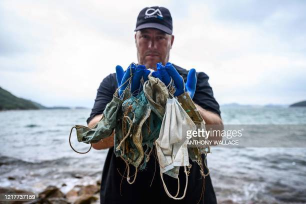 In this photo taken on May 13 Gary Stokes founder of the environmental group Oceans Asia poses with discarded face masks he found on a beach in the...