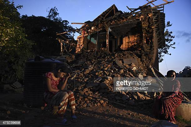 In this photo taken on May 13 Nepalese residents Januka Khanal and Rojina Parajuli sit among the ruins of one of the three houses in the village of...