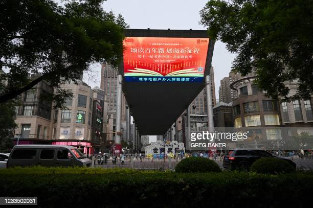 """In this photo taken on May 19 a large screen shows a propaganda slogan which reads """"Praising and reading hundred-year road; Looking forward to a new..."""