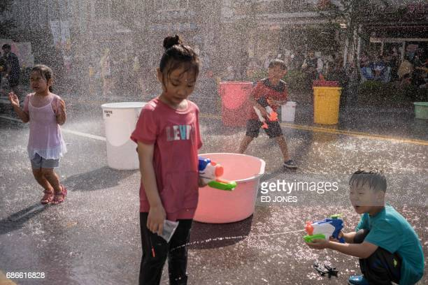 In this photo taken on May 21 a boy sprays water at a girl during a water fight organised to mark the opening of the weeklong International Mime...