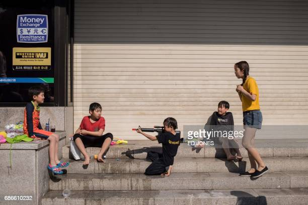 In this photo taken on May 21 a child points a water gun following a water fight organised to mark the opening of the weeklong International Mime...