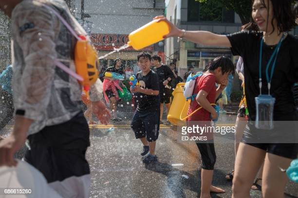 In this photo taken on May 21 people take part in a water fight organised to mark the opening of the weeklong International Mime Festival in...
