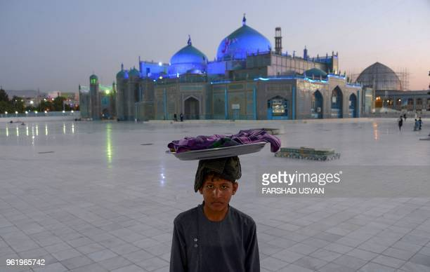 TOPSHOT In this photo taken on May 23 an Afghan Bolani vendor looks on as he waits for customers in the courtyard of Hazrate Ali shrine or 'Blue...