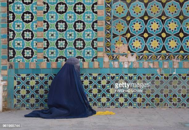 TOPSHOT In this photo taken on May 23 an Afghan burqaclad woman sits in the courtyard of Hazrate Ali shrine or 'Blue Mosque' during the holy month of...