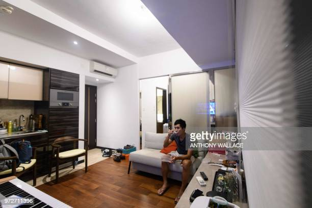 In this photo taken on May 23 finance worker Adrian Law eats a delivered meal while watching television in his studio apartment for which he paid...