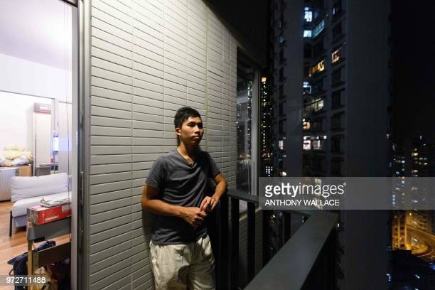 In this photo taken on May 23 finance worker Adrian Law looks out at the view from the balcony of his studio apartment for which he paid more than...