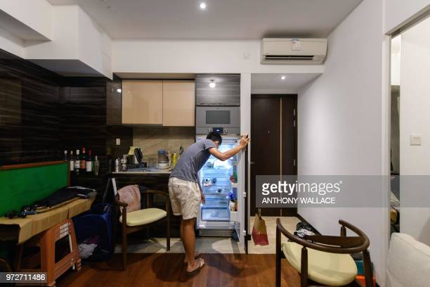 In this photo taken on May 23 finance worker Adrian Law opens the fridge in the kitchen area of his studio apartment for which he paid more than...