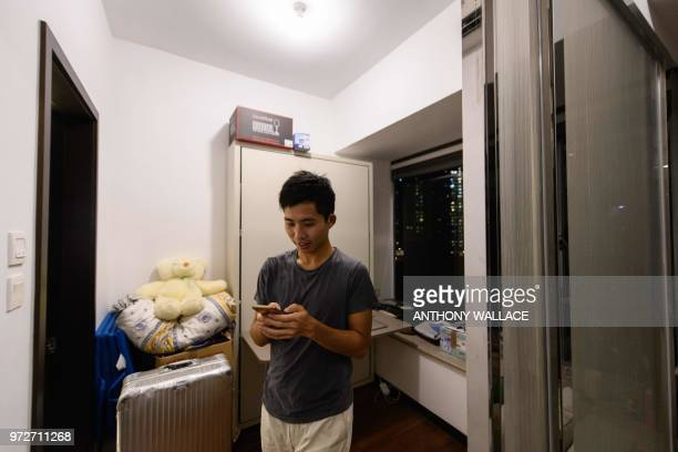 In this photo taken on May 23 finance worker Adrian Law uses his phone as he stands in the bedroom of his studio apartment for which he paid more...