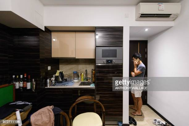 In this photo taken on May 23 finance worker Adrian Law uses his phone to order a meal delivery in his studio apartment for which he paid more than...