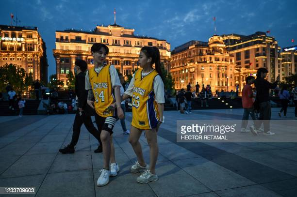 In this photo taken on May 25 a couple wearing National Basketball Association jerseys visit the promenade on the Bund along the Huangpu River in...