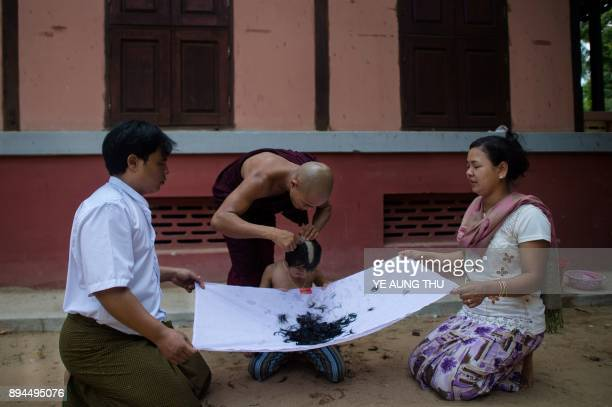 In this photo taken on May 25 the parents of a soontobe monk hold a sheet to collect the hair shaved from his head during a ceremony initiating him...