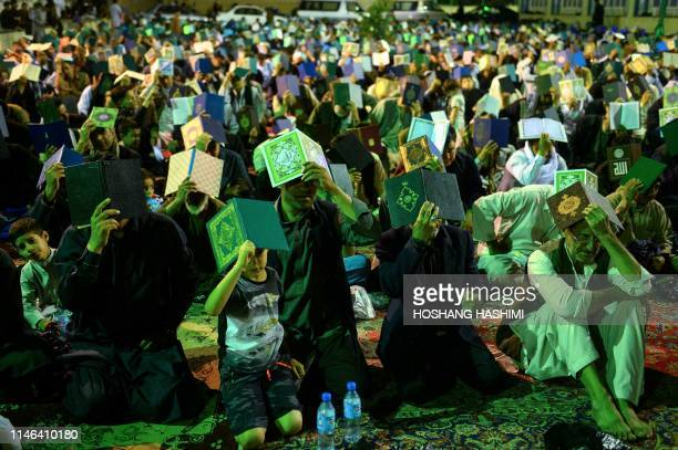 In this photo taken on May 26 Afghan Shiite Muslim worshippers hold copies of the holy Quran as they pray during the Laylat alQadr at a mosque in...