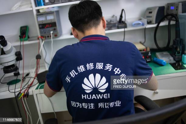 In this photo taken on May 27 a worker wearing a Huawei shirt fixes phones at a retail store in Beijing China is digging in for a tough period of...