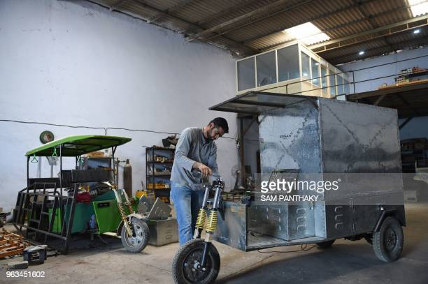 In this photo taken on May 28 an Indian engineer assembles an ETransport Vehicle at Savy Electric Vehicles manufacturing facility on the outskirts of...