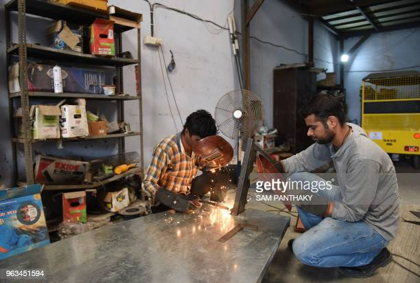 In this photo taken on May 28 an Indian engineer looks on as a worker welds a platform of an EVehicle at Savy Electric Vehicles manufacturing...