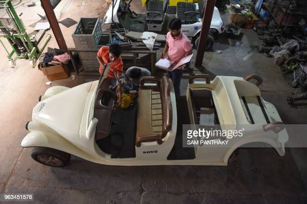In this photo taken on May 28 founder and CEO of Savy Electric Vehicles Chandan Mundhra looks on as engineers attend an EVintage Campus Golf Cart at...