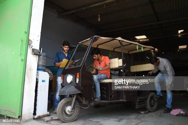 In this photo taken on May 28 Indian engineers check parts of an EPassenger Rickshaw at Savy Electric Vehicles manufacturing facility on the...