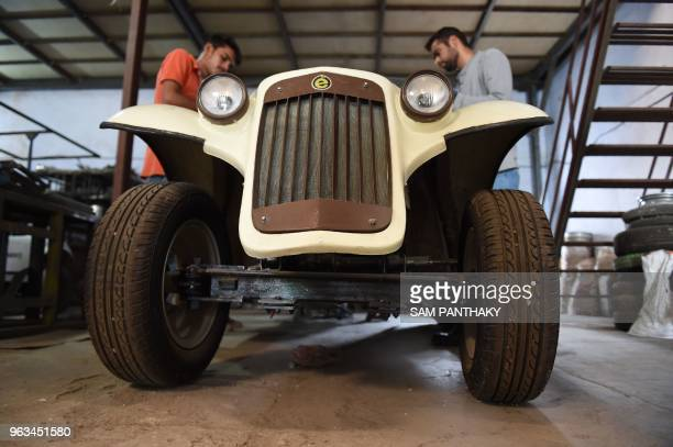 In this photo taken on May 28 Indian engineers of Savy Electric Vehicles attend an EVintage Campus Golf Cart at the company's manufacturing facility...