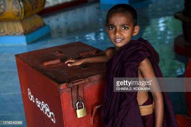 In this photo taken on May 29 2020 a young monk poses at the Dimbulagala Raja Maha temple in the east of the island on the eve of Buddhist 'Poson'...
