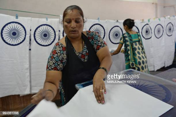 In this photo taken on May 9 Nirmala S Ilkal prepares to screen print the central strip of the Indian national flag at the Khadi Gramodyog Samyukta...