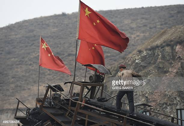 TOPSHOT In this photo taken on November 20 a worker clears a conveyer belt used to transport coal near a coal mine at Datong in China's northern...