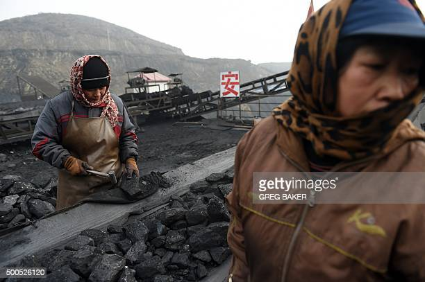 In this photo taken on November 20 workers sort coal on a conveyer belt near a coal mine at Datong in China's northern Shanxi province For decades...