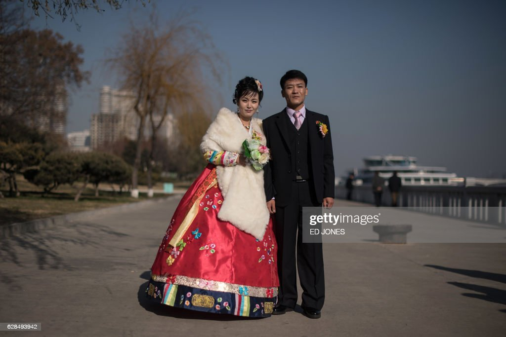 In this photo taken on November 25, 2016, groom Sip Seung-chul (R) stands with his bride as they prepare to attend a wedding photo shoot on the Taedong river in Pyongyang. / AFP PHOTO / Ed JONES / This photo package is accompanied by a blog piece written by staff photographer Ed Jones https://goo.gl/lEZ8Fk