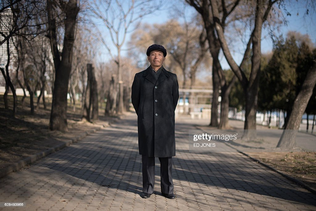 In this photo taken on November 27, 2016, retiree Kim Hong-Sol (Kim Hong-sul) poses for a photo on a pathway near the Taedong river in Pyongyang. / AFP / Ed JONES / This photo package is accompanied by a blog piece written by staff photographer Ed Jones https://goo.gl/lEZ8Fk