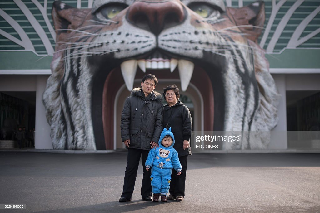 In this photo taken on November 27, 2016, toddler Mun Ji-Song (Moon Ji-sung) (C) poses for a photo with his parents at the entrance to the Central Zoo in Pyongyang. / AFP / Ed JONES / This photo package is accompanied by a blog piece written by staff photographer Ed Jones https://goo.gl/lEZ8Fk
