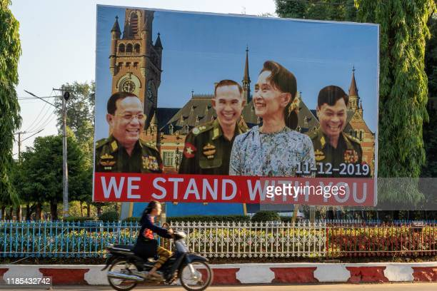 In this photo taken on November 28 a woman on motorcycle rides past a huge billboard depicting Myanmar State Counsellor Aung San Su Kyi with the...