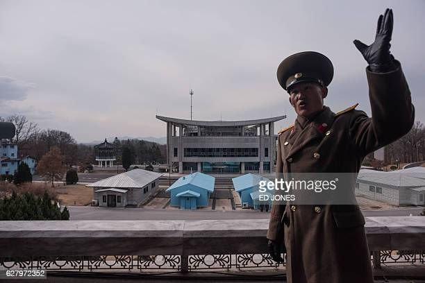 In this photo taken on November 30 a Korean People's Army soldier gestures before the joint security area and Demilitarized Zone separating North and...
