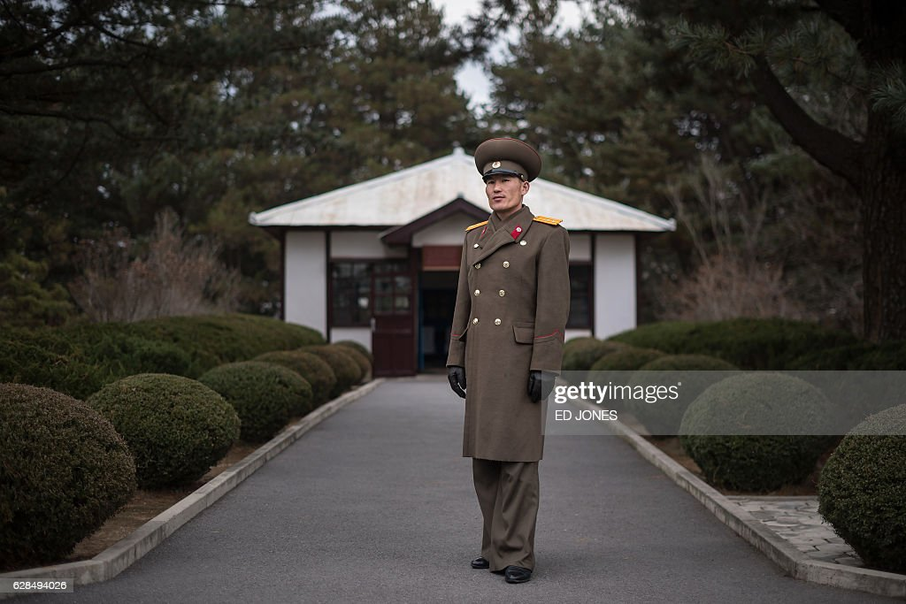 In this photo taken on November 30, 2016, Korean People's Army (KPA) liutenant and tour guide Hwang Myong-Jin (Hwang Myong-jin) poses for a photo in front of a hut where negotiations for the Korean War armistice agreement were held in 1953, at Panmunjom near the Demilitarized Zone (DMZ) separating North and South Korea. / AFP / Ed JONES / This photo package is accompanied by a blog piece written by staff photographer Ed Jones https://goo.gl/lEZ8Fk