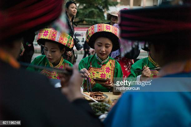 In this photo taken on November 4 dancers of the Miao ethnic minority in traditional costumes attend a banquet at the end of their New Year festival...