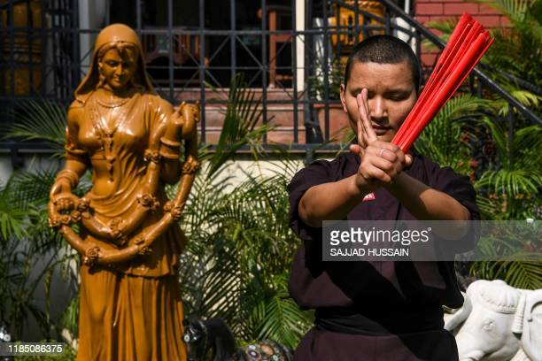 In this photo taken on November 5 a member of the Kung Fu Nuns group demonstrates her skills in New Delhi They train with swords and machetes after...