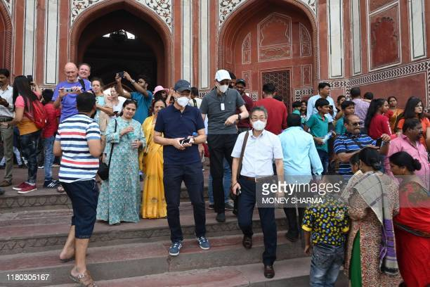 In this photo taken on November 5 tourists wear face masks to protect against air pollution as they visit the Taj Mahal in Agra. - India's top court...