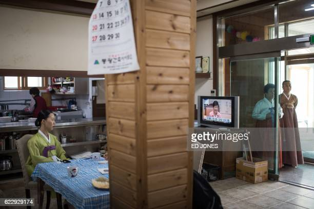 In this photo taken on November 8 shaman Min HyeGyeong watches a television news coverage of the political scandal surrounding South Korea's...