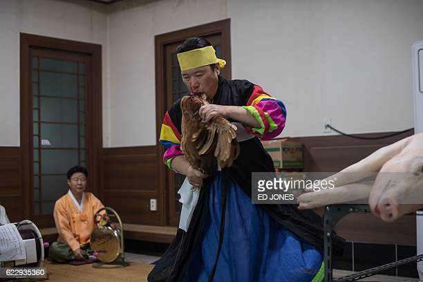 In this photo taken on November 8 shaman Shin JoongIn bites the head from a live chicken as he performs a ritual in which offerings are made to...