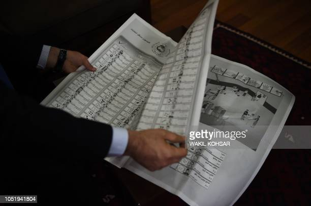 In this photo taken on October 10 an Afghan employee of the Independent Election Commission shows a newspapersized ballot paper at a warehouse in...