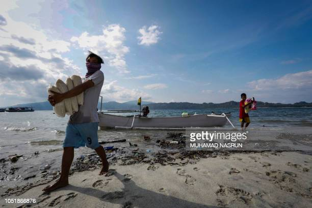 In this photo taken on October 10 Indonesian villagers carry aid provisions delivered by boat to isolated Lambonga village in Donggala following the...