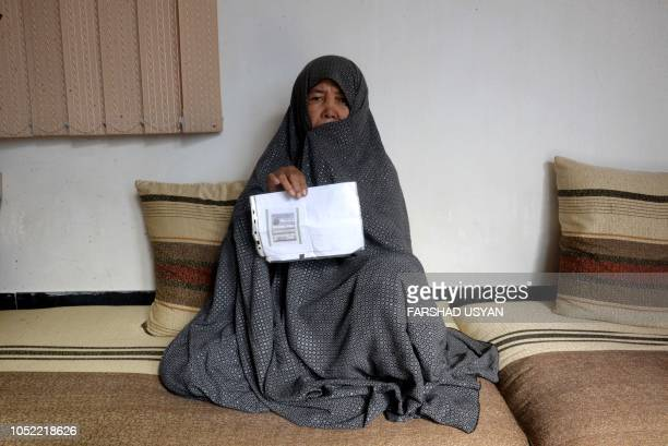 In this photo taken on October 11 2018 Afghan housewife Fatimah poses for a picture as she holds her ID card or Tazkira registered to vote in the...