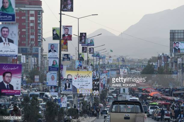 In this photo taken on October 15 Afghan commuters drive along a road with posters of candidates hanging from posts during the legislative election...