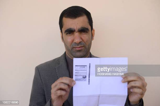 In this photo taken on October 15 Afghan public servant Ghulam Farooq Adil poses for a picture as he holds his id card or Tazkira registered to vote...
