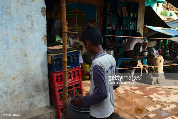 In this photo taken on October 16, 2020 a young boy stands along a street before collecting clothes used to wrap dead bodies for the final rites, at...