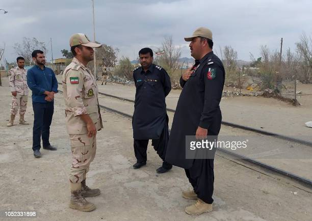In this photo taken on October 16 a Pakistani border security official and an Iranian border official meet at Zero Point in the PakistanIran border...