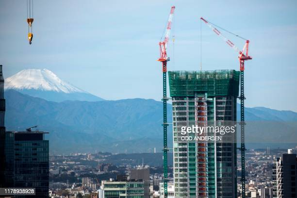 In this photo taken on October 26 Mount Fuji is seen from Tokyo behind construction sites of new highrise buildings in the Japanese capital As Japans...