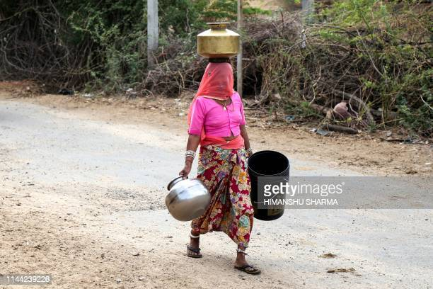TOPSHOT In this photo taken on on May 16 an Indian woman carries buckets and containers to collect drinking water from a road side water tap on the...