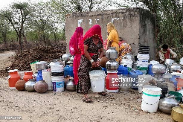 In this photo taken on on May 16 Indian villagers collect drinking water from a road side water tap on the outskirts village of Ajmer, in the Indian...