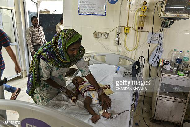 In this photo taken on September 15 2015 Indian patient Anus lies on a bed as his mother assists him with an oxygen mask in the dengue ward of a...