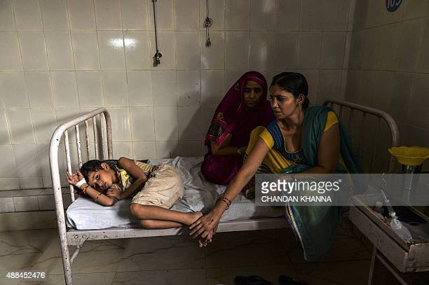 In this photo taken on September 15 2015 Indian patient Nikhil Tomar lies on a bed as his mother sits in the dengue ward of a government hospital in...