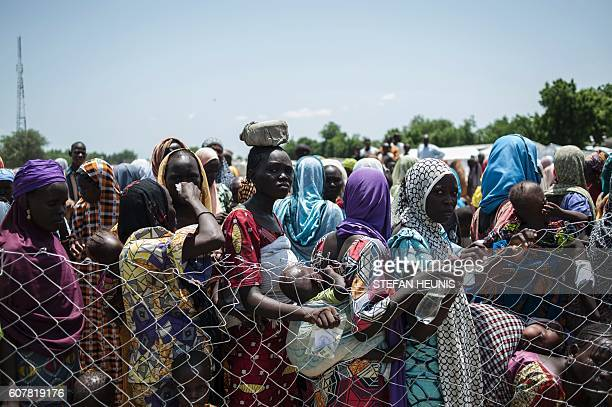 TOPSHOT In this photo taken on September 15 women and children queue to enter one of the Unicef nutrition clinics in Muna informal settlement which...